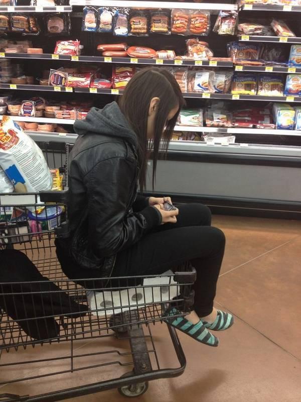 jovem sentada no papel higiênico no carrinho de supermercado