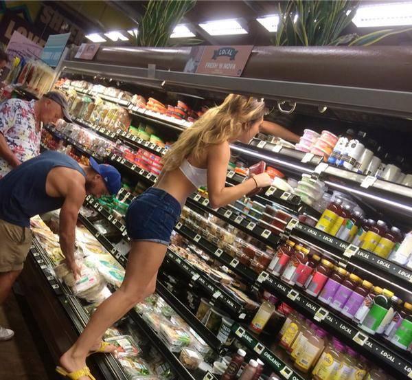 garota subindo na prateleira do supermercado
